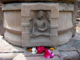 Flower offerings to a statue of Buddha in Sarnath, the location where Buddha met his first disciples